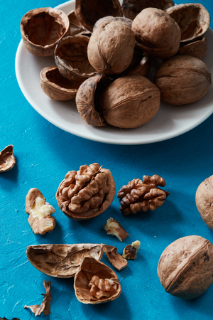 Close-up of walnuts and kernels with plate of nutshells on rustic color backdrop. Healthy raw snack or organic vegetarian meal ingredients.