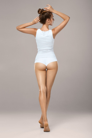 Studio HD capture of a beautiful young woman in underwear. Perfect slim tanned body - an example of sports, dieting, fitness or plastic surgery and aesthetic cosmetology