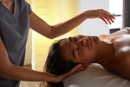 Close up shot of a professional masseuse doing face and head massage for her male client. Handsome young man relaxing receiving facial massage at the spa center. Relaxation therapy resort recreation. Stock Photo