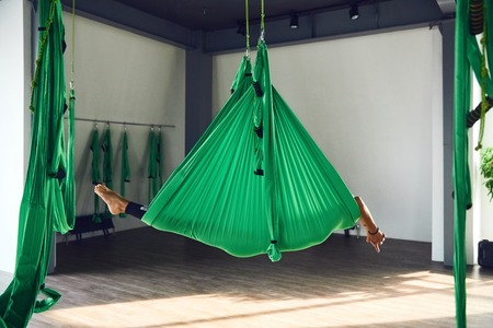 The interior shooting of an adult woman practices different inversion antigravity yoga with a hammock in yoga studio. The balance between mental and physical, one person effort and achievement concept 版權商用圖片