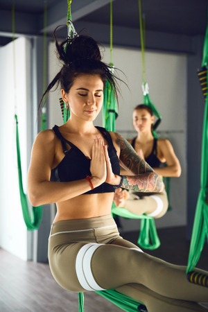 The interior shooting of an two women practices different inversion antigravity yoga with a hammock in yoga studio. The balance between mental and physical, one person effort and achievement concept