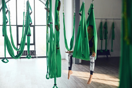 The interior shooting of senior woman practices different inversion antigravity yoga with a hammock in yoga studio. The balance between mental and physical, one person effort and achievement concept