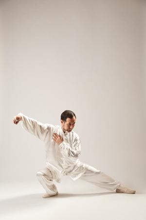 Senior master practicing qi qong taijiquan at studio. Breathing exercise and martial art moves, traditional chinese qi energy management gymnastics