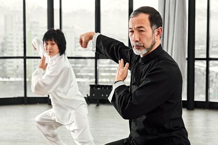 Couple de maîtres seniors pratiquant le qi qong taijiquan au studio. Exercice de respiration et mouvements d'arts martiaux, gymnastique traditionnelle chinoise de gestion de l'énergie qi.