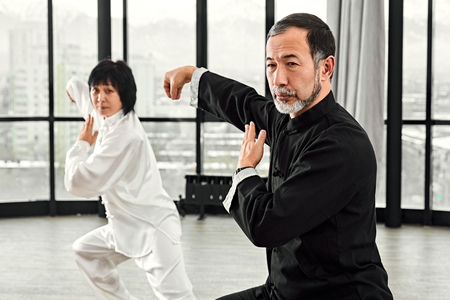 Couple of senior masters practicing qi qong taijiquan at studio. Breathing exercise and martial art moves, traditional chinese qi energy management gymnastics. 免版税图像