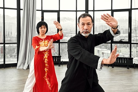 Couple of senior masters practicing qi qong taijiquan at studio. Breathing exercise and martial art moves, traditional chinese qi energy management gymnastics. Stock Photo