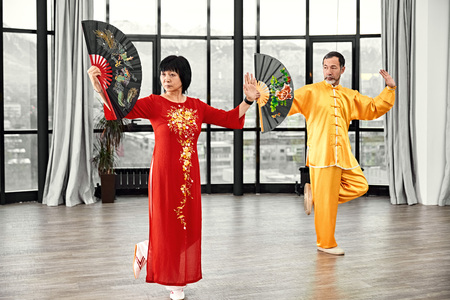 Couple of senior masters practicing qi qong taijiquan at studio. Breathing exercise and martial art moves, traditional chinese qi energy management gymnastics. Фото со стока