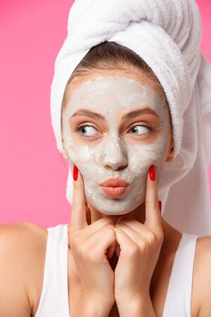 Young woman with towel wrapped around her head applying clay face mask and having fun. Daily morning routine - facial cleaning, skin care, peeling, moisturising and beauty treatment concept Фото со стока