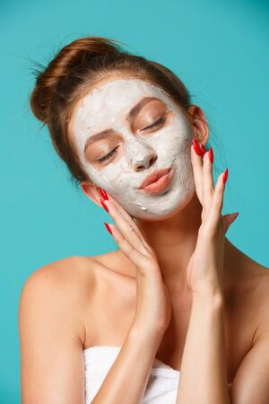 Young woman with towel wrapped around her body applying clay face mask and having fun. Daily morning routine - facial cleaning, skin care, peeling, moisturising and beauty treatment concept