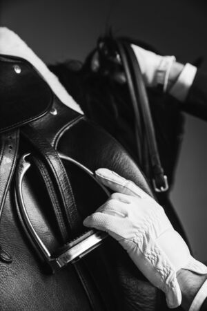 Jockey saddle up the thoroughbred horse for dressage or equestrian race. Stirrup, reins and hand on the mane. Noble aesthetics, dress code, professional equipment, competition and excitement concept