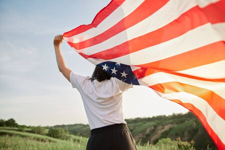4th of July. Fourth of July. Joyful woman with the national American flag against beautiful landmark. Independence Day. Patriotic holiday, democracy respect and veteran respect concept