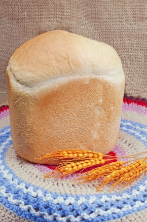 Bread and ears of corn on the background of bright cloth Stock Photo