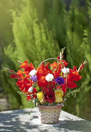 A bright bouquet of roses and gladiolus on green garden