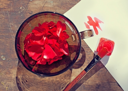 Borrow the colors of nature  rose petals in a bowl and a paint of the same color Stock Photo