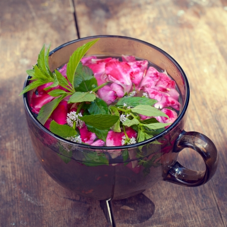 the cup of tea with rose petals and mint on old wooden background