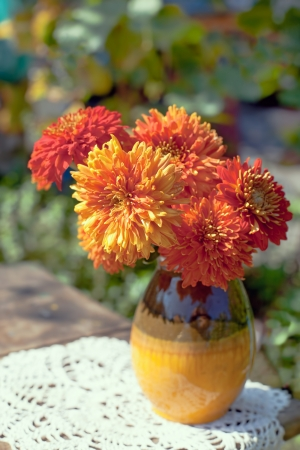The Autumn bouquet  The Bright Chrysanthemums in a ceramic vase on a background of a green garden