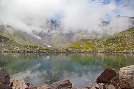 Alpine lake in the fog  Karachay–Cherkessia, Greater Caucasus, Russia