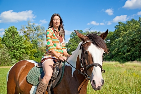 riding horse: A young girl dressed as an Indian rides a paint horse Stock Photo