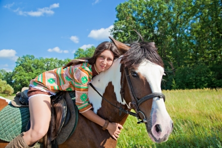 dapple horse: A young girl dressed as an Indian rides a paint horse Stock Photo