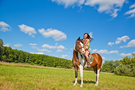 A young girl dressed as an Indian rides a paint horse Stock Photo