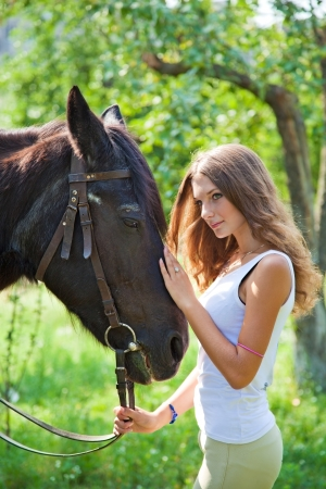 Young girl walking with a horse in the garden.