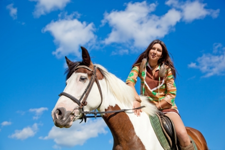 A young girl dressed as an Indian rides a paint horse  Focus on horses face  photo