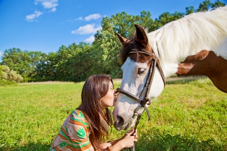 A young girl dressed as an Indian kisses horse Stock Photo