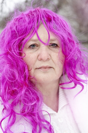 Portrait of an elderly woman in a pink wig Stock Photo