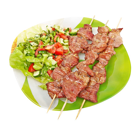 kebab and salad on a green plate, isolated on white background Stock Photo