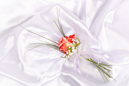Wedding boutonniere on white silk background