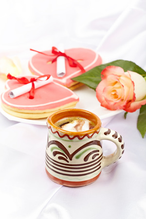 Coffee, heart shaped cookies with notes, rose. Pleasant breakfast for a loved one. Stock Photo