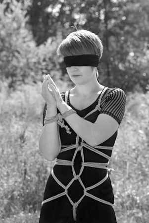 Bound woman with his hands tied and blindfolded. Shibari. Stock Photo