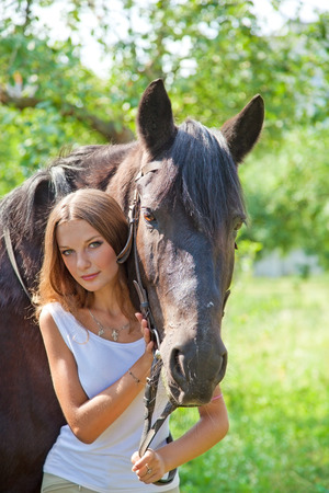 Young beautiful girl walking in the park with a horse photo