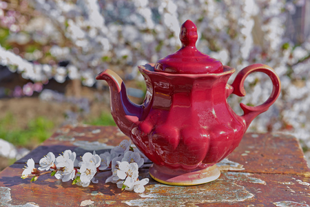 Old teapot on a wooden table. Shabby chic style.