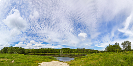 complement: Small lake and the forest. Landscape complement a variety and beautiful clouds. Stock Photo