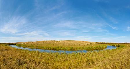A small prairie river Big Melik. Cows graze on the banks. Saratov region, Russia.