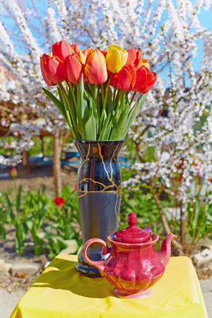 Bouquet of tulips and old teapot on yellow tablecloth. Behind blossoming spring garden background.