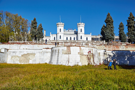 SHAROVKA, UKRAINE - CIRCA OCTOBER 2015: The White Swan palace on blue sky background. Tourists walk around the castle.