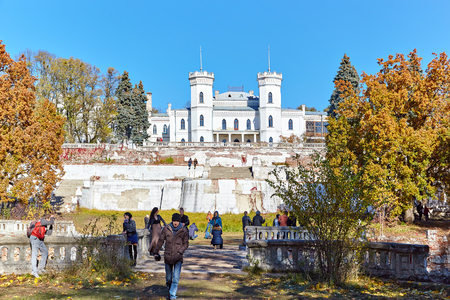 SHAROVKA, UKRAINE - CIRCA OCTOBER 2015: The White Swan palace on blue sky background. Tourists walk and take photo around the castle.