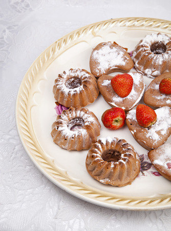 Muffins with strawberries on a old plate