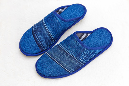 Blue denim slippers on a white sheep wool rug