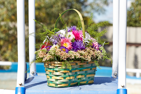 Aster bouquet in a green basket near the pool