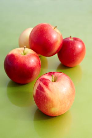 Red apples on a green background Reklamní fotografie