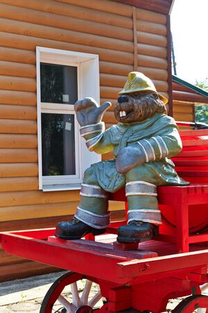 A figurine of a fireman's beaver on a cart with a barrel and a pump. Entrance to the museum of fires. Voronezh Nature Reserve, Russia.