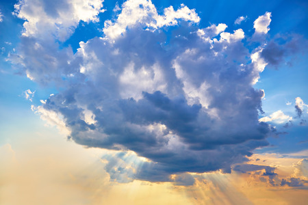The sun's rays make their way through a huge cumulus cloud. Abstract nature background. Reklamní fotografie