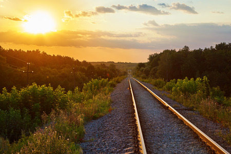A single-track railway in the middle of the forest. Sunset, backlight.