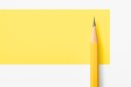 Beautiful top view close up macro photography of wooden yellow pencil isolated on yellow and white paper with copy space to look minimalism and clean. Flash light made smooth shadow from yellow pencil. Stock Photo