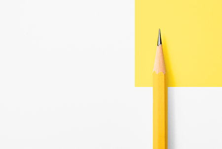 Beautiful top view close up macro photography of wooden yellow pencil isolated on yellow and white paper with copy space to look minimalism and clean. Flash light made smooth shadow from yellow pencil. Banque d'images
