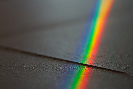 Close up macro photo of so beautiful rainbow glare spectrum lighting specular reflection on the floor. Sun ray shining through window glass that work as prism and reflex colorful spectrum on floor.