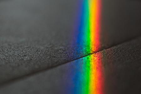 Sluit omhoog macrofoto van zo mooi spectrum die van de regenboogglans spiegelende bezinning over de vloer aansteken. Zonstraal schijnt door vensterglas dat werkt als prisma en reflex kleurrijke spectrum op vloer.